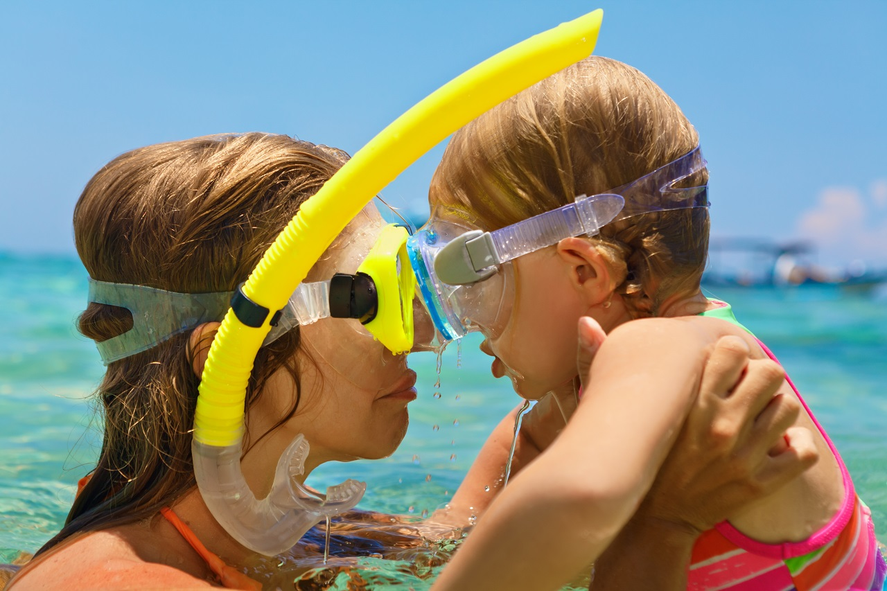 Happy-family-mother-baby-girl-in-snorkeling-masks-on-sea-beach-of-tropical-island