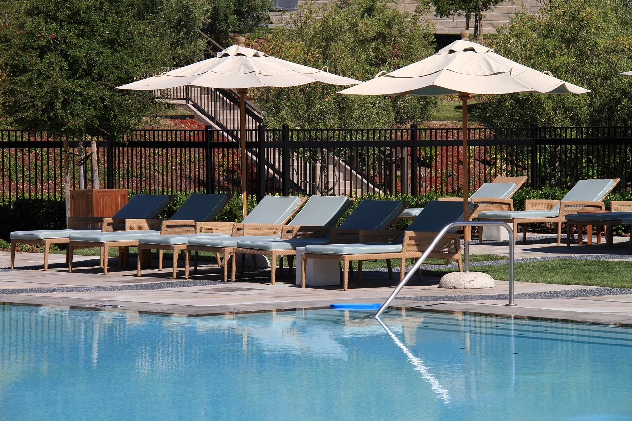 Inviting-upscale-pool-and-patio-with-lounge-chairs-and-umbrellas