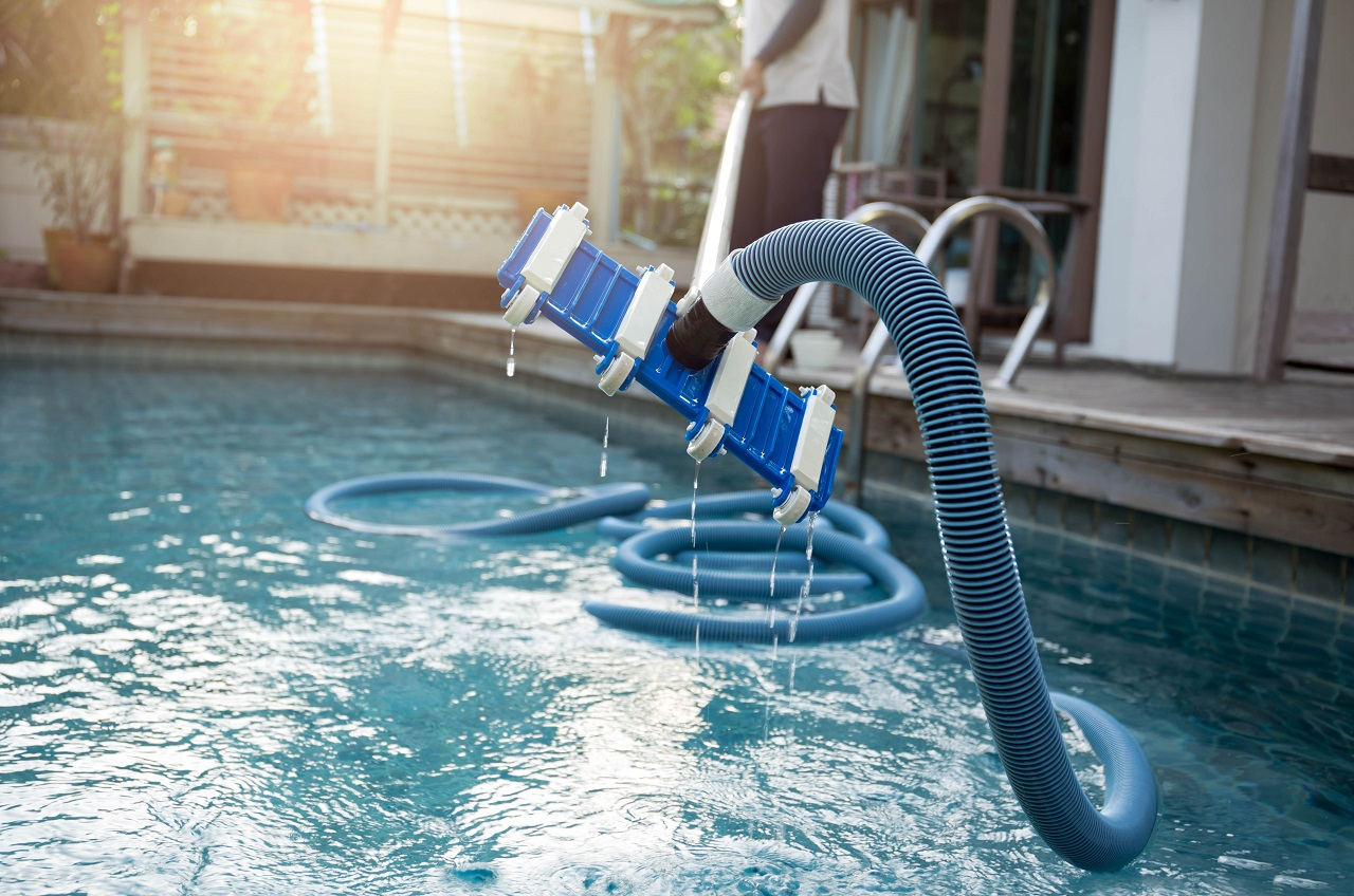 Man-cleaning-swimming-pool-with-vacuum-tube-cleaner-early-in-the-morning