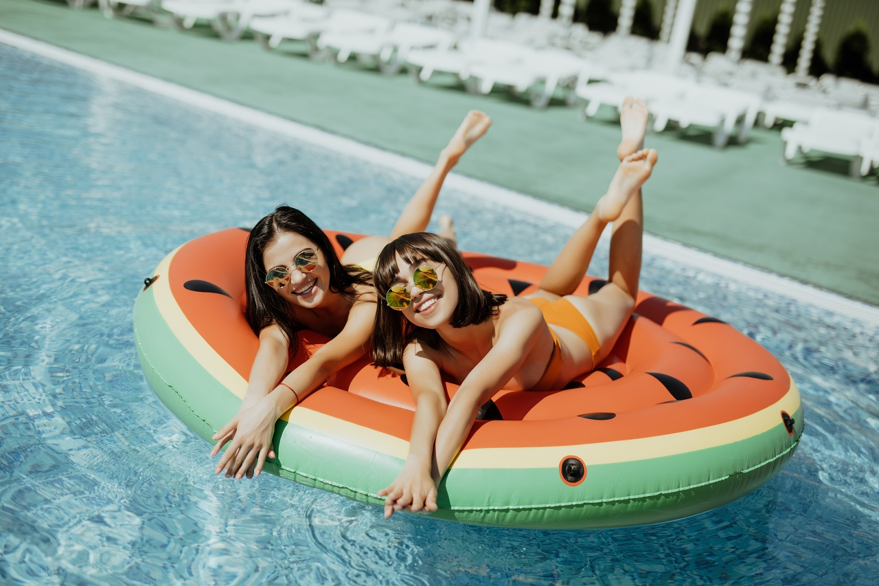 Portrait-of-female-friends-lying-on-an-inflatable-toy-sunbathing-on-floating-pool