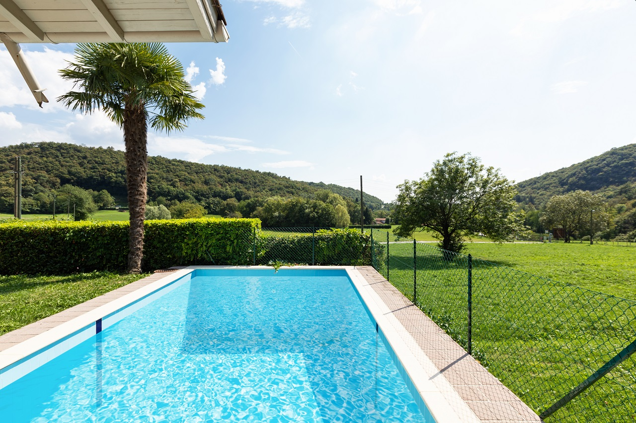 Villa-with-pool-and-surrounded-by-green-lawn-on-a-summer-day