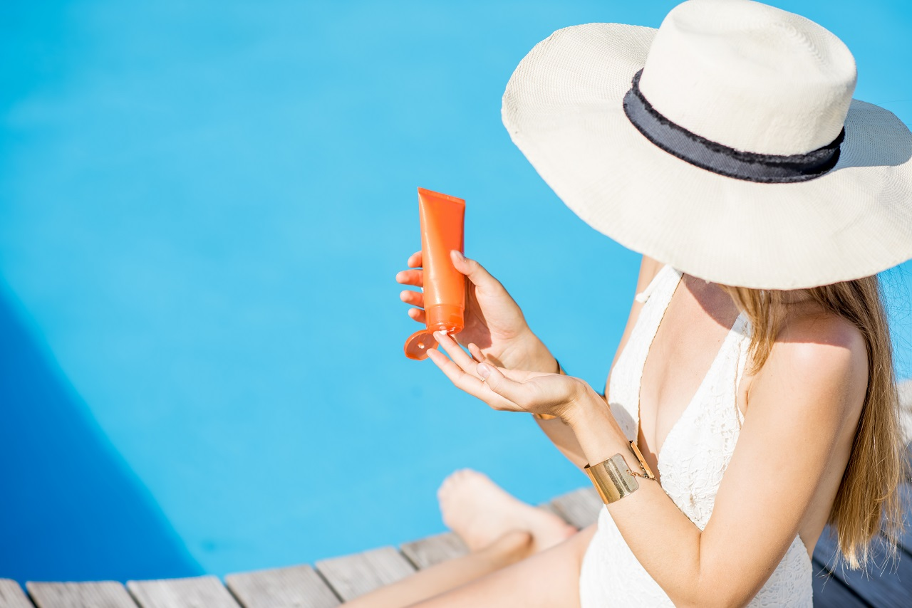 Young-beautiful-woman-applying-sunscreen-lotion-sitting-on-the-wooden-poolside.-Sunscreen-solar-cream-uv-protection-concept