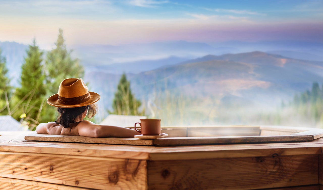 Young-woman-in-an-open-air-bath-with-view-of-the-mountains