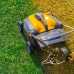 Aeration-of-the-lawn-in-the-garden.-Yellow-aerator-on-green-grass