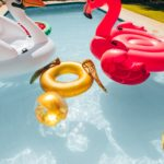 Group-of-colorful-inflatable-toys-floating-in-a-swimming-pool-on-a-summer-day.-Inflatable-swan-flamingo-ring-and-ball-in-pool-scaled