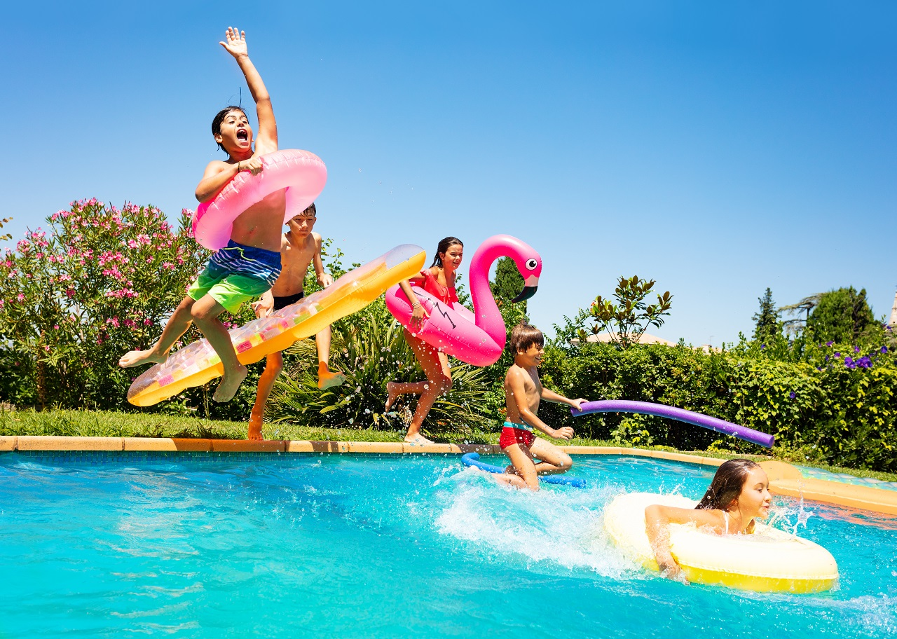 Happy-friends-jumping-in-pool-on-the-vacations