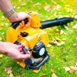 Starting-a-handheld-cordless-electric-leaf-blower-in-a-garden-selective-focus.-Autumn-fall-gardening-works-in-a-backyard